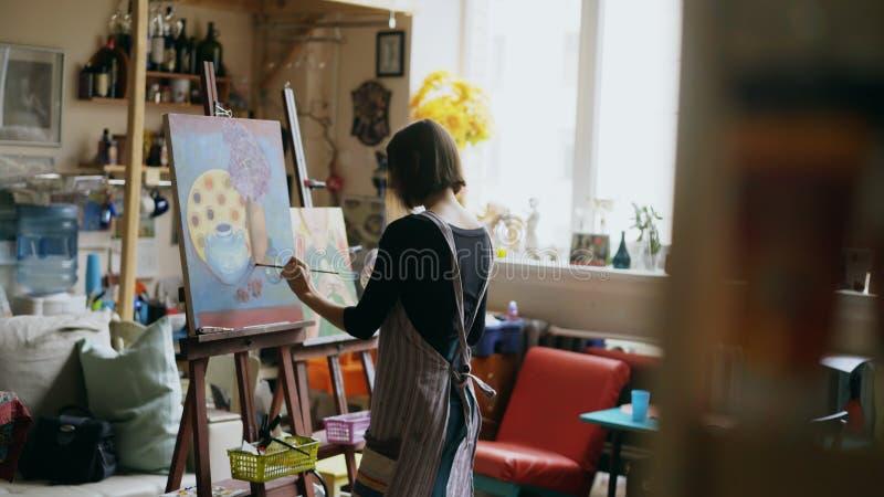 Bakre sikt av den unga målareflickan i bild för förklädemålningstilleben på kanfas i konst-grupp arkivbild