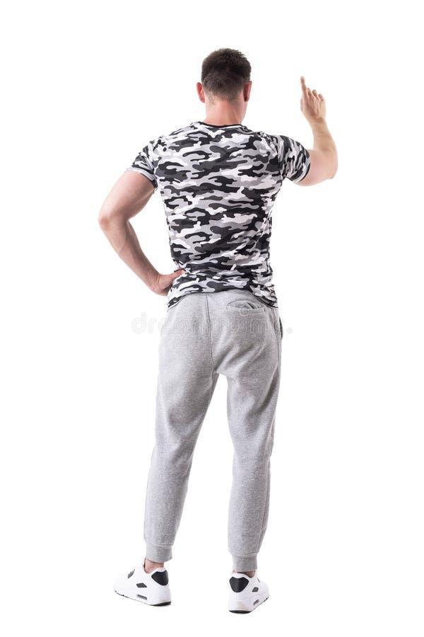 Bakre sikt av den unga mannen i sportswear med tryckknappen som pekar fingergest royaltyfri fotografi