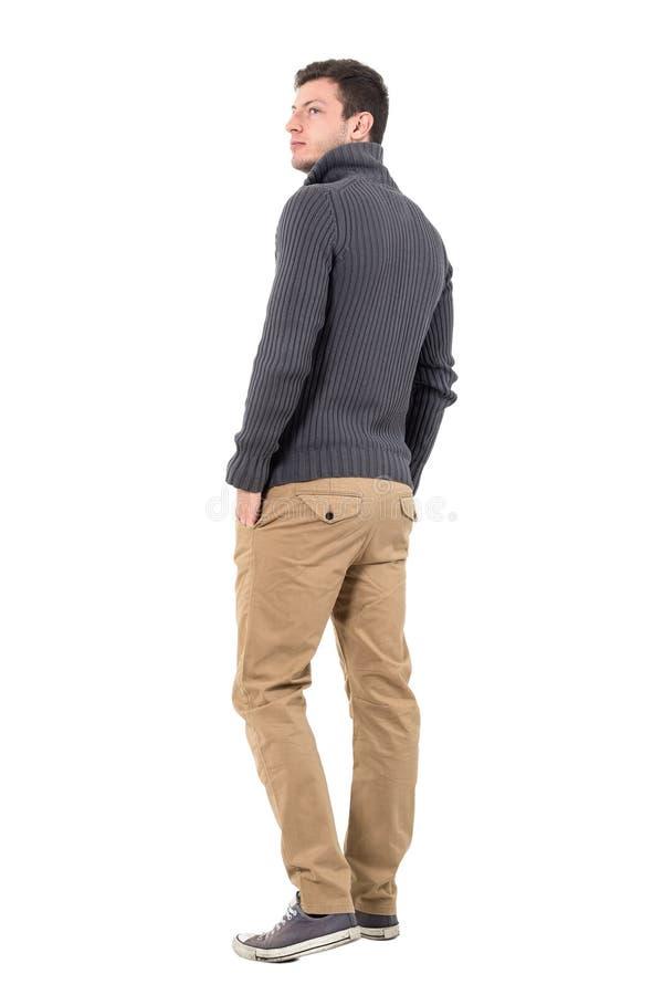 Bakre sikt av den unga tillfälliga mannen i den gråa tröjan som ser upp över skuldra royaltyfria bilder