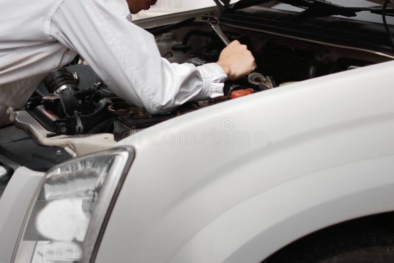 Bakre sikt av den yrkesmässiga unga mekanikermannen i likformig med skiftnyckeln som diagnostiserar motorn mot bilen i öppen huv  royaltyfri foto