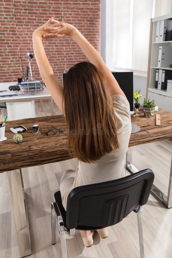 Bakre sikt av en affärskvinna Stretching Her Arms royaltyfria foton