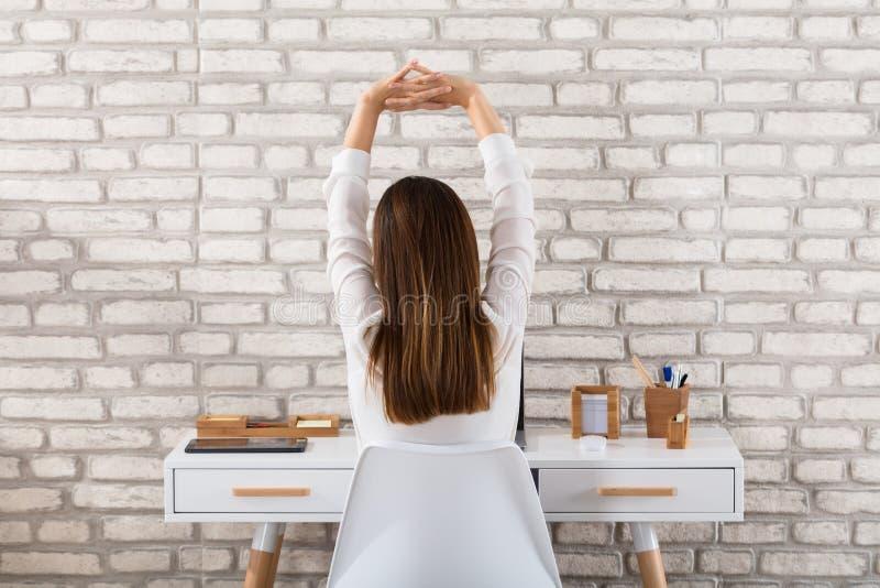 Bakre sikt av en affärskvinna Stretching Her Arms fotografering för bildbyråer