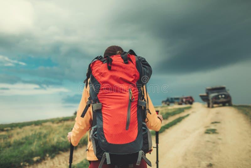 Bakre sikt av en aktiv ung kvinna som går i bergen arkivfoton