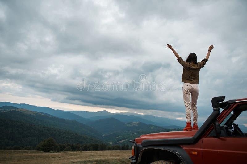 Bakre sikt av en angenäm kvinna som tycker om frihet i bergen royaltyfri fotografi