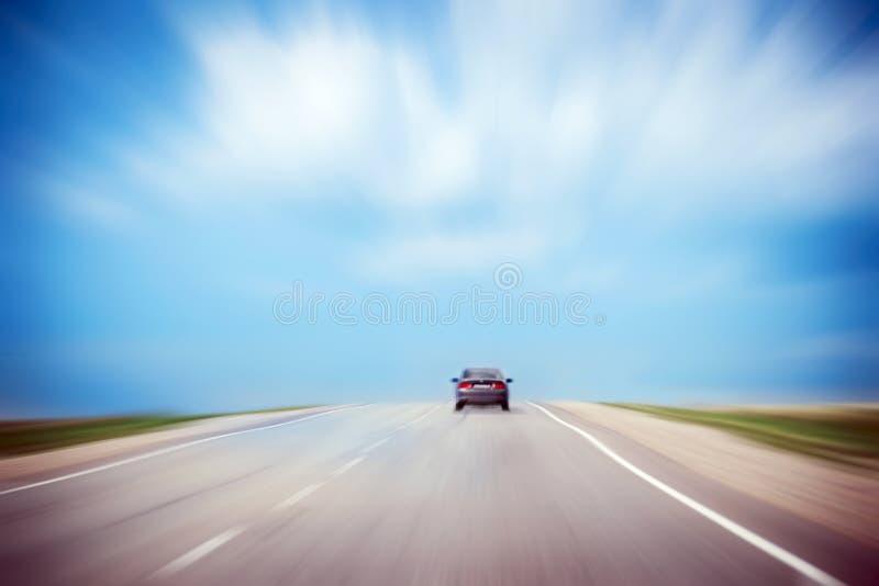 Bakre sikt av en bil som rusar på asfaltvägen i bygd Molnig stormig dramatisk himmel Kopia-utrymme bakgrundsblur suddighetdde rör fotografering för bildbyråer