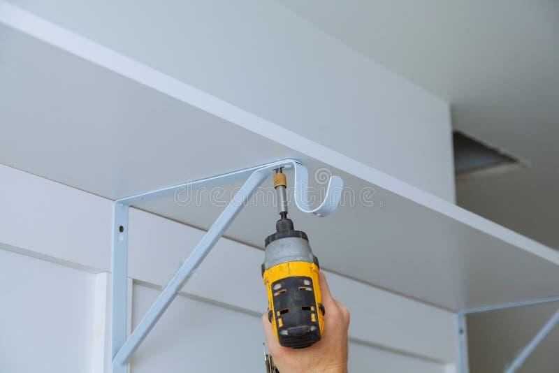 Bakre sikt av en faktotum som använder en maktdrillborr för att installera en hylla på en vägg royaltyfri fotografi