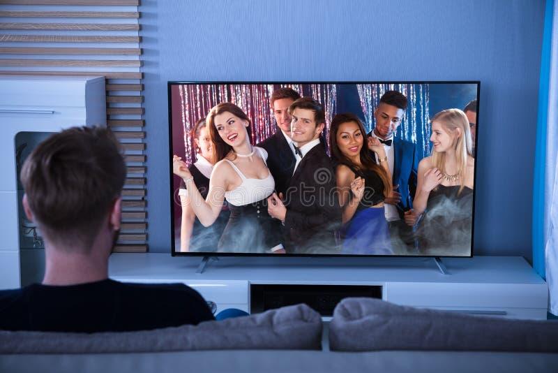 Bakre sikt av en hållande ögonen på television för man royaltyfria foton
