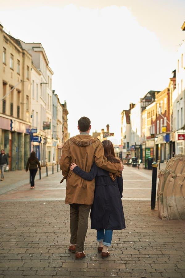Bakre sikt av en kontur av ett älska par som kramar, medan besöka en destinationsstad som promenerar den gamla gatan av engelska arkivfoton
