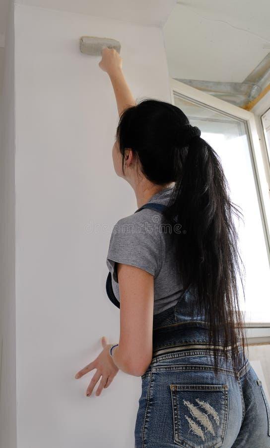 Bakre sikt av en kvinna som målar en vägg royaltyfria foton