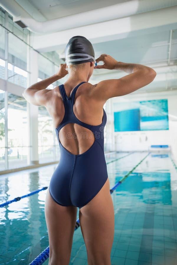 Bakre sikt av en kvinnlig simmare vid pölen på fritidmitten arkivfoto