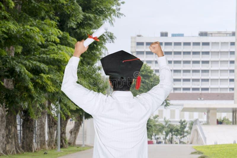 Bakre sikt av en man som firar hans avläggande av examen royaltyfri foto