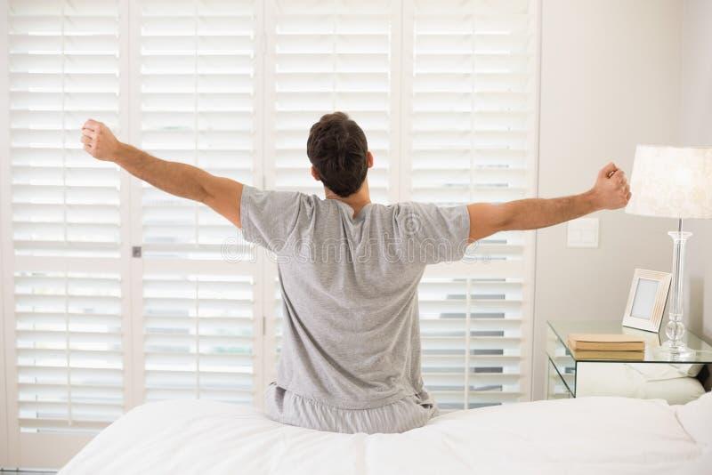 Bakre sikt av en man som sträcker hans armar i säng arkivbilder