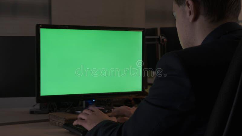 Bakre sikt av en manlig arbetare för ungt kontor som sitter på hans skrivbordarbete på datoren, chromakeybildskärm Materiell?ngd  arkivbilder