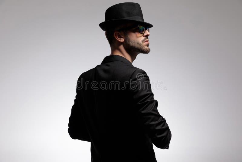 Bakre sikt av en mystisk man som ser till sidan fotografering för bildbyråer