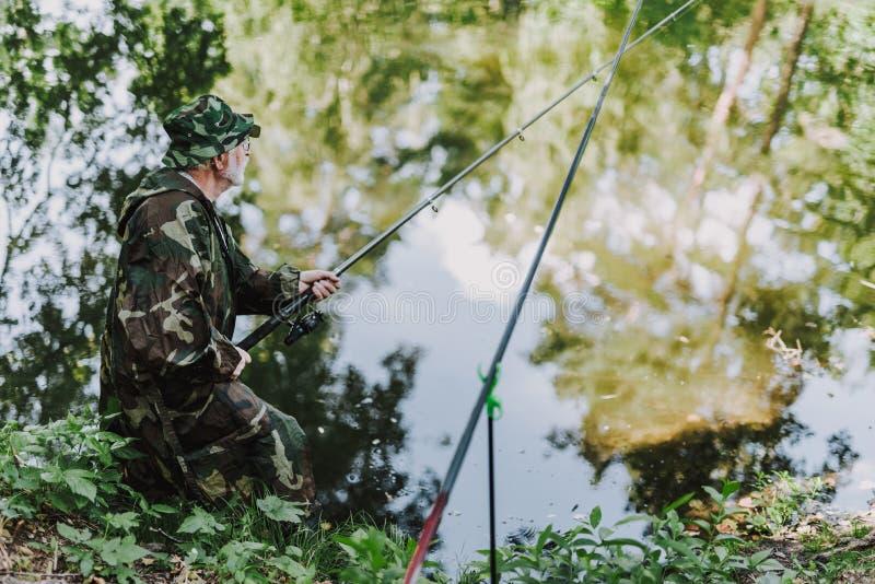 Bakre sikt av en pensionerad sportfiskare som har att fiska helg arkivfoton