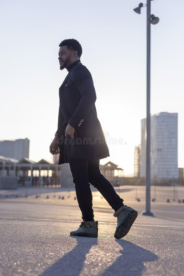 Bakre sikt av en svart ung skäggig man som utomhus går, medan se bort arkivfoto