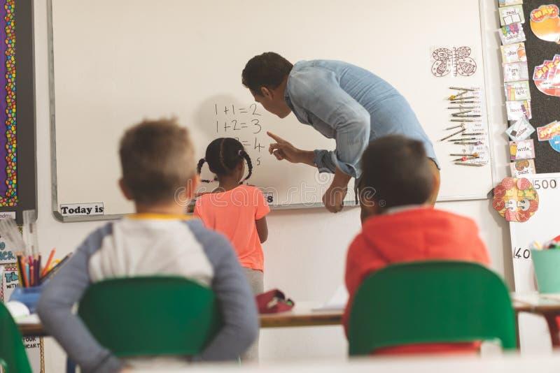 Bakre sikt av en undervisande matematik för Caucasian lärare till en av hans skolaunge på en whiteboard royaltyfri bild