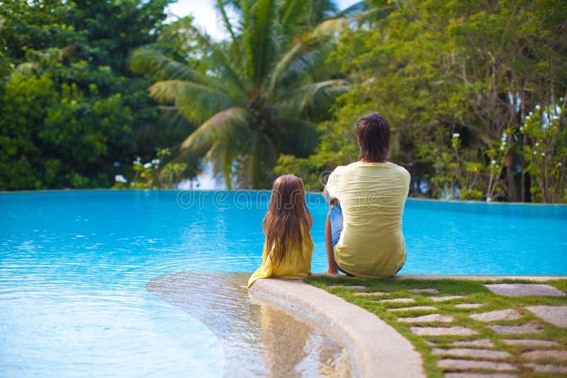 Bakre sikt av en ung fader och hans gulliga dotter arkivfoto