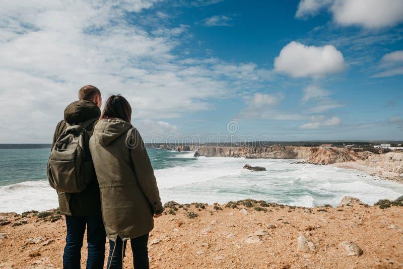 Bakre sikt av ett ungt par av turister eller handelsresande arkivfoton