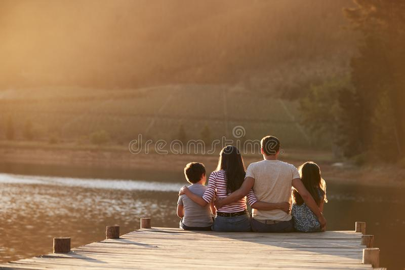 Bakre sikt av familjanseendet på träbryggan vid sjön arkivbilder