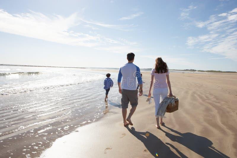 Bakre sikt av familjen som promenerar stranden med picknickkorgen royaltyfri foto