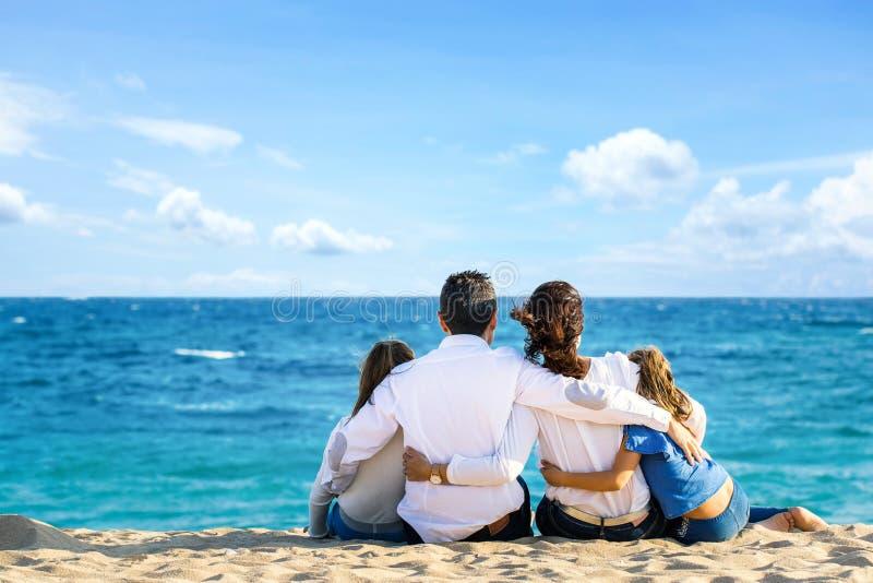 Bakre sikt av familjen som tillsammans sitter på stranden som ser horisonten arkivfoton
