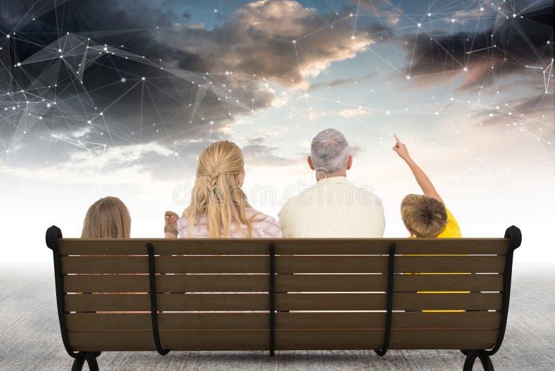 Bakre sikt av familjsammanträde på bänk mot stjärnakonstellationer royaltyfri fotografi