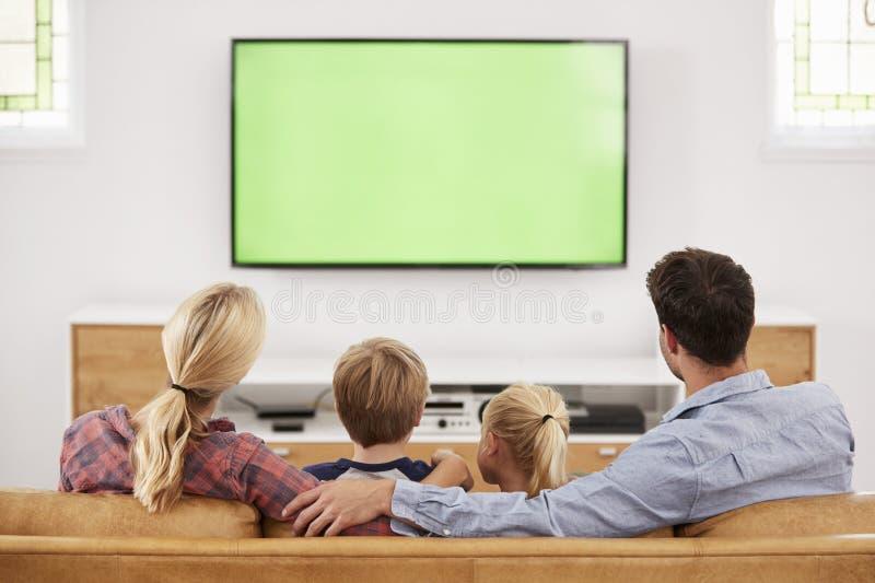 Bakre sikt av familjsammanträde på Sofa In Lounge Watching Televisio royaltyfri fotografi