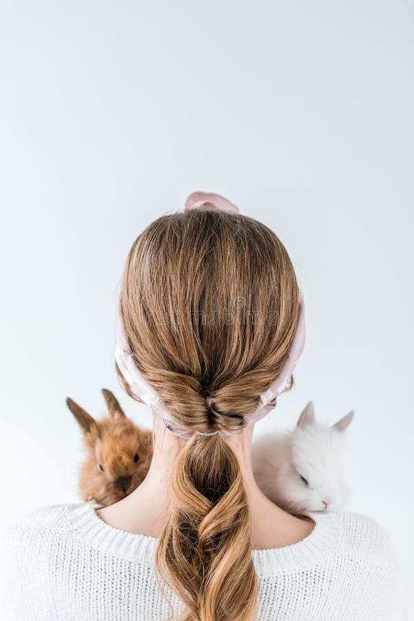 Bakre sikt av flickan som rymmer förtjusande päls- kaniner arkivbilder
