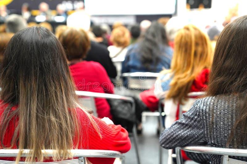 Bakre sikt av folk i ett möte eller en konferens fotografering för bildbyråer