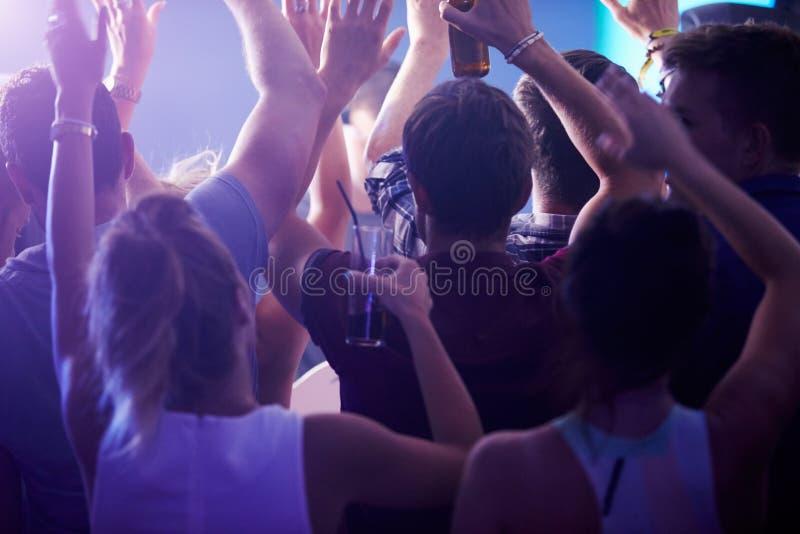 Bakre sikt av folk som dansar i nattklubb royaltyfri fotografi