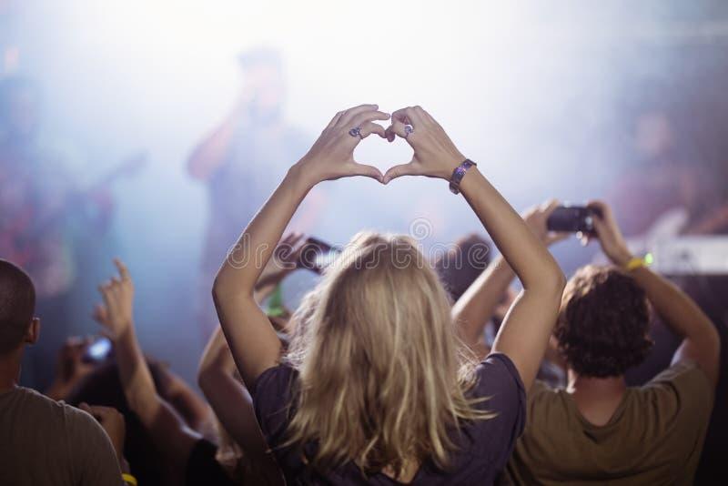 Bakre sikt av form för kvinnadanandehjärta, medan tycka om på nattklubben royaltyfri fotografi