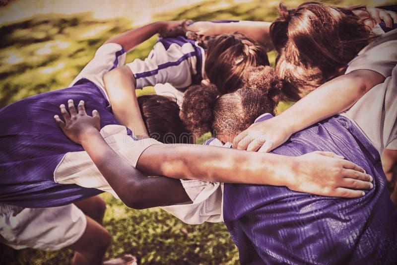 Bakre sikt av fotbolllaget som bildar bråteet royaltyfri foto