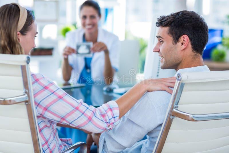 Bakre sikt av gravida kvinnan och hennes make som diskuterar med doktorn arkivbild