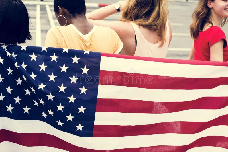 Bakre sikt av gruppen av den olika kvinnagruppen med amerikanska flaggan arkivfoto
