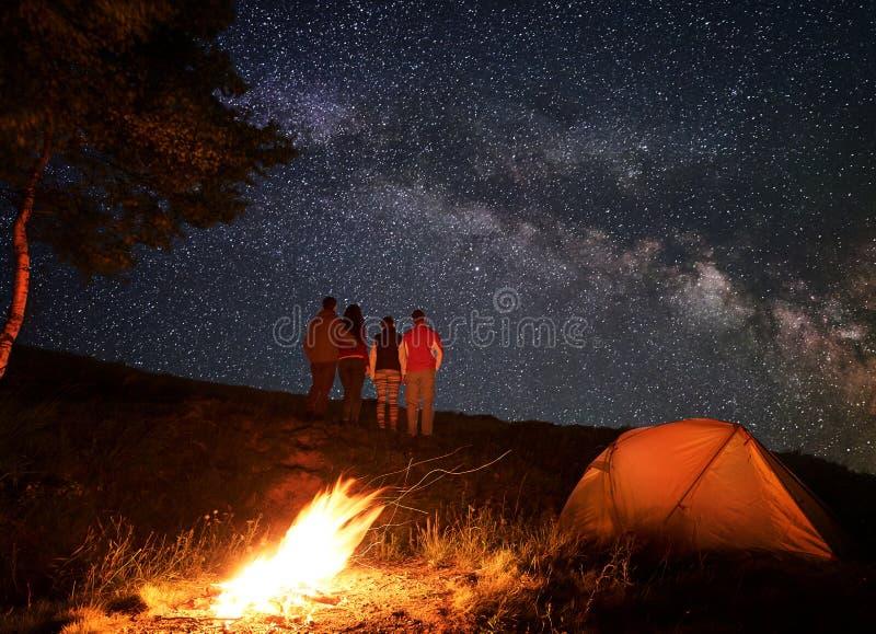 Bakre sikt av gruppturister som ser stjärnklar himmel som är den synliga mjölkaktiga vägen under natt av att campa fotografering för bildbyråer