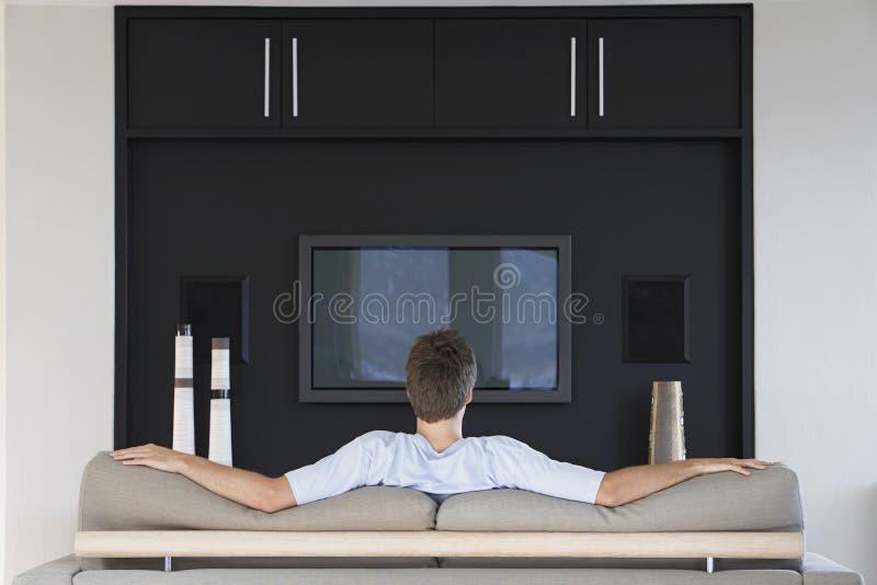 Bakre sikt av hållande ögonen på television för man royaltyfri bild