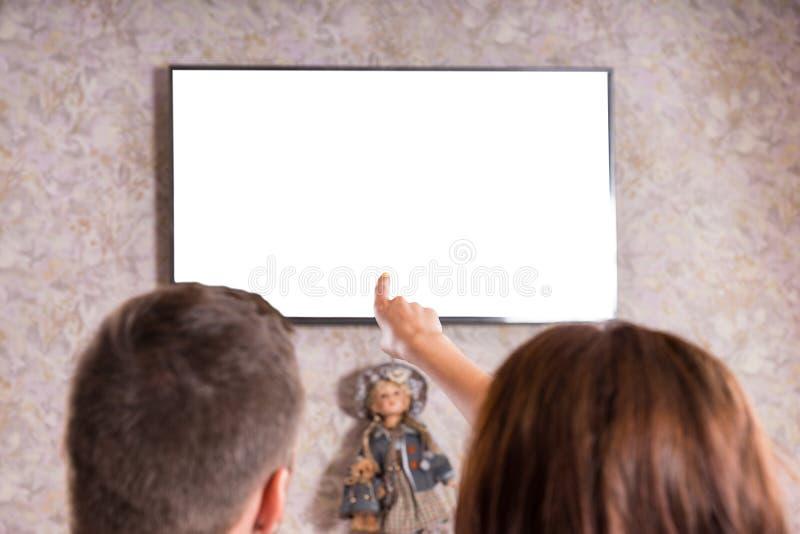 Bakre sikt av hållande ögonen på television för par tillsammans arkivfoto