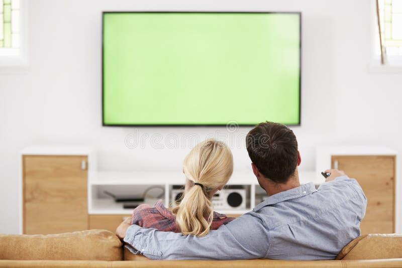 Bakre sikt av hållande ögonen på television för par tillsammans royaltyfria foton
