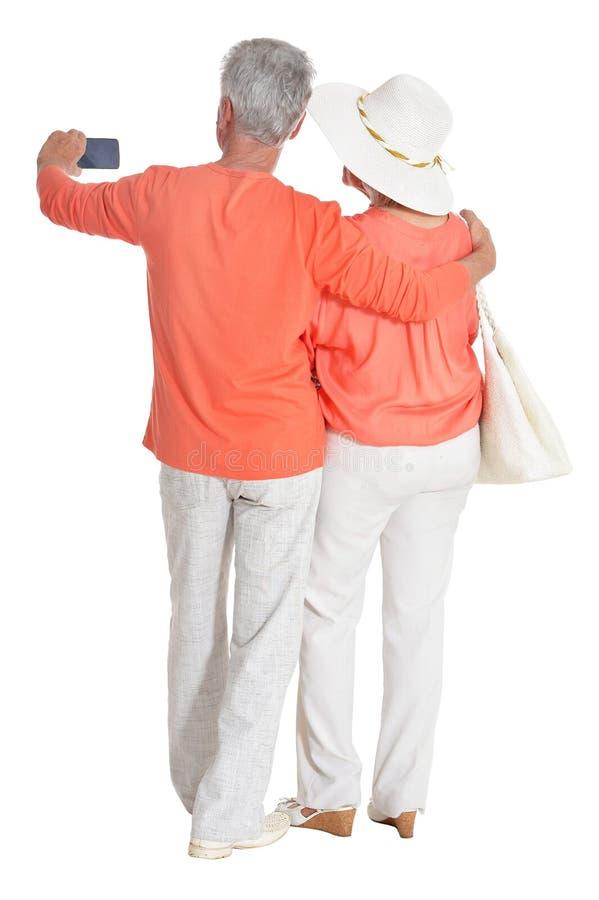 Bakre sikt av höga par som kramar och tar selfie royaltyfri fotografi