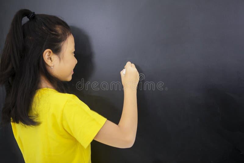 Bakre sikt av handstil för kvinnlig student på en svart tavla royaltyfri foto