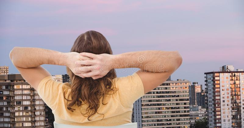 Bakre sikt av hipsteren med händer bak huvudet mot byggnader arkivfoto