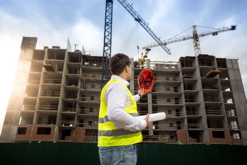 Bakre sikt av konstruktionsteknikern som poserar på byggnadsplats på su arkivfoto