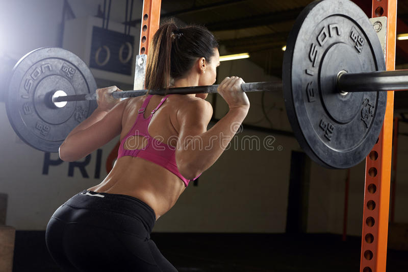 Bakre sikt av kvinnan i idrottshalllyftande vikter på skivstång royaltyfri bild