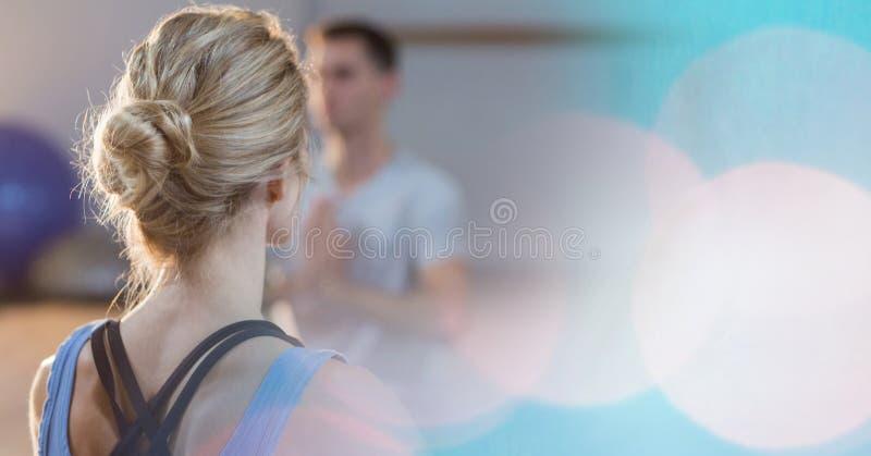 Bakre sikt av kvinnan med praktiserande yoga för hårbulle i bokeh royaltyfri fotografi
