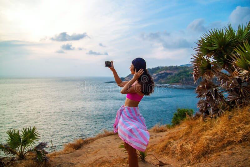 Bakre sikt av kvinnan som fotograferar havet med den smarta telefonen, medan stå på skeppet mot blå himmel arkivbilder