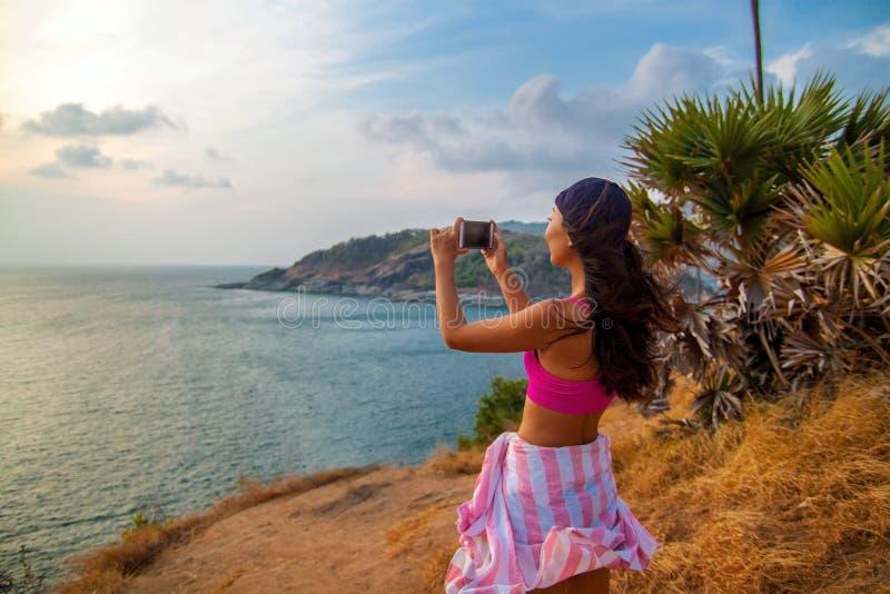 Bakre sikt av kvinnan som fotograferar havet med den smarta telefonen, medan stå på skeppet mot blå himmel fotografering för bildbyråer