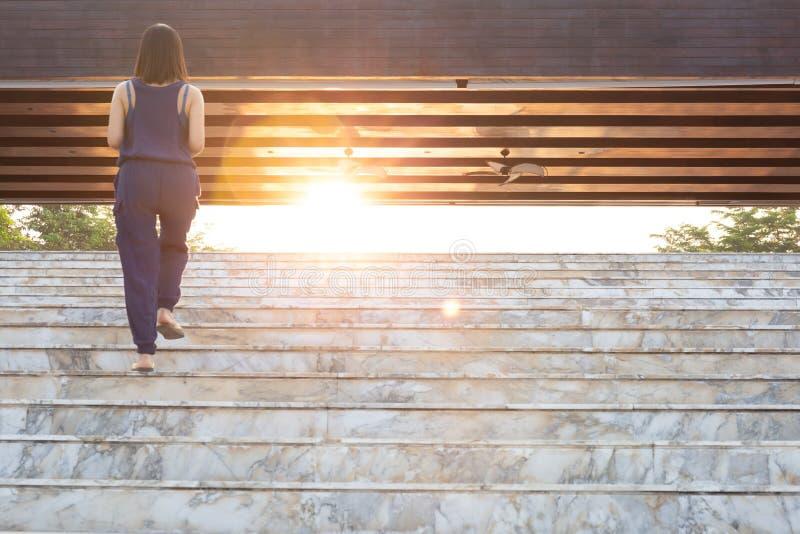 Bakre sikt av kvinnan som går upp trappan med ljus biljettpris royaltyfri fotografi