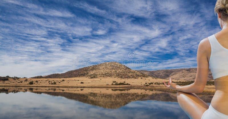 Bakre sikt av kvinnan som mediterar vid sjön mot himmel royaltyfri foto