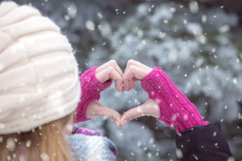 Bakre sikt av kvinnan som skapade hjärta med händer snöig dag royaltyfri foto